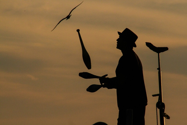 Silhouette of a Juggling Street Performer and His Unicycle at Sunset